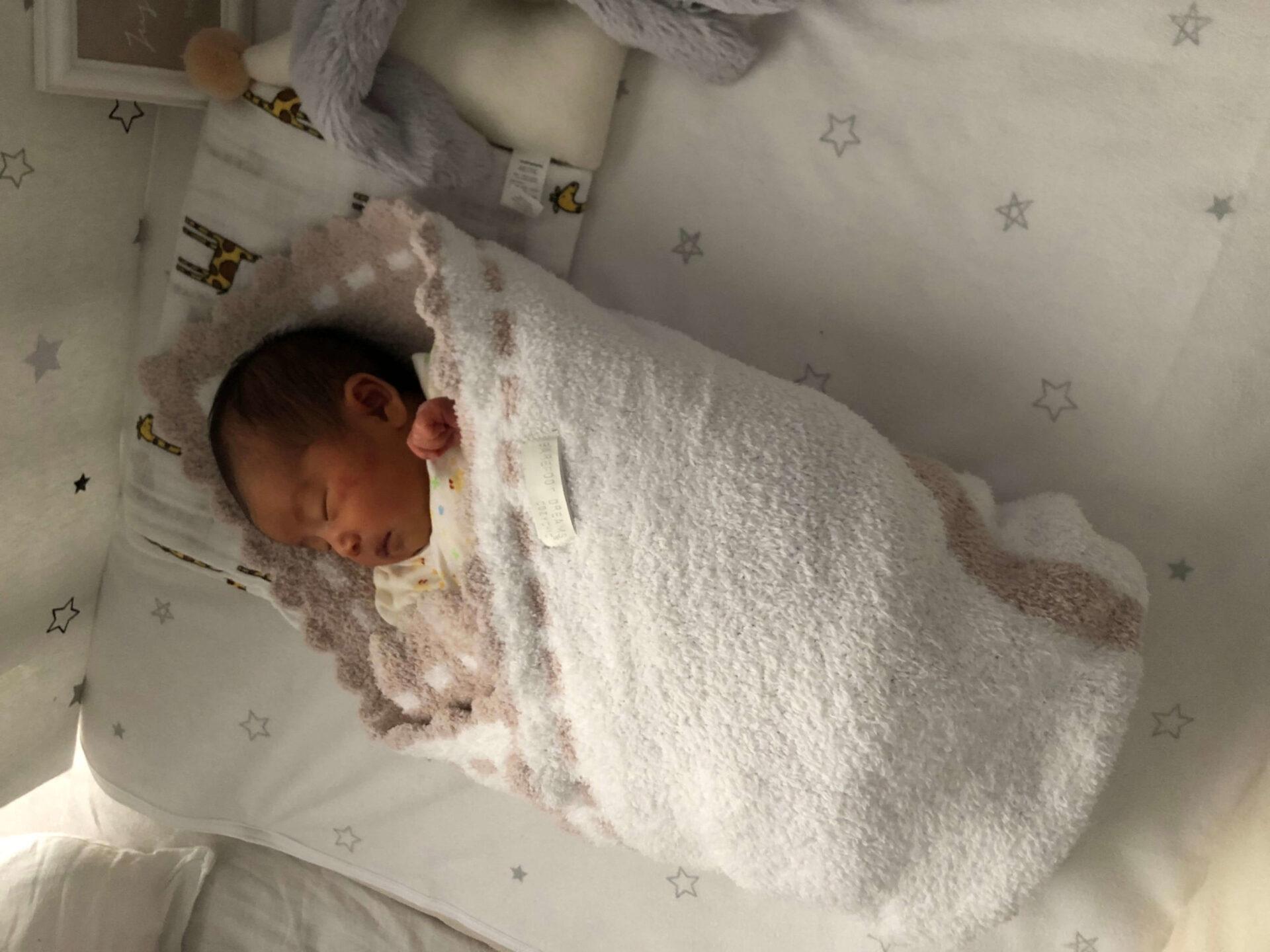 ベビーベッドで寝ている新生児のユノ